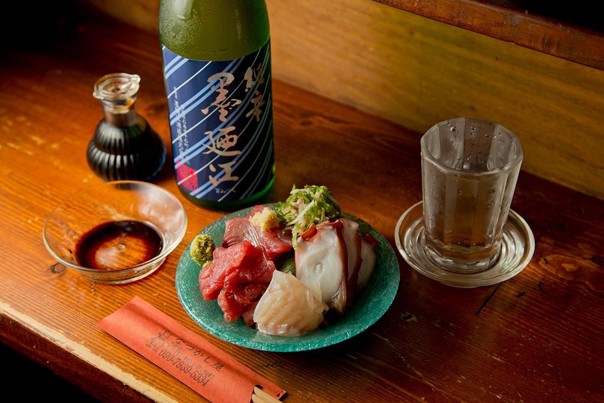 小山のように盛られた「刺身盛り合わせ」(950円)と「墨廼江純米大辛口」(グラス700円)。